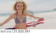 Купить «Front view of Caucasian woman with waving American flag dancing on the beach 4k», видеоролик № 31920581, снято 12 ноября 2018 г. (c) Wavebreak Media / Фотобанк Лори