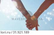 Купить «Couple hand in hand surrounded by bokeh effect», видеоролик № 31921189, снято 5 марта 2019 г. (c) Wavebreak Media / Фотобанк Лори