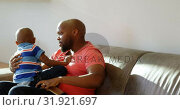 Купить «Father and son playing together in living room at home 4k», видеоролик № 31921697, снято 6 июня 2018 г. (c) Wavebreak Media / Фотобанк Лори