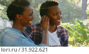 Купить «Twin sisters listening music on earphones in the park 4k», видеоролик № 31922621, снято 6 мая 2018 г. (c) Wavebreak Media / Фотобанк Лори