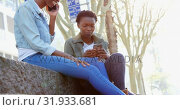 Купить «Twin sisters using mobile phone in the city 4k», видеоролик № 31933681, снято 6 мая 2018 г. (c) Wavebreak Media / Фотобанк Лори