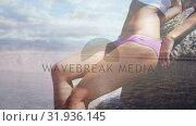 Купить «Woman leaning on a rock at the shore», видеоролик № 31936145, снято 17 апреля 2019 г. (c) Wavebreak Media / Фотобанк Лори