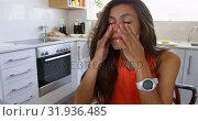 Купить «Beautiful woman sitting with hands on face at dining table in kitchen at home 4k», видеоролик № 31936485, снято 17 января 2019 г. (c) Wavebreak Media / Фотобанк Лори