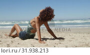 Side view of young African american woman relaxing on the beach 4k. Стоковое видео, агентство Wavebreak Media / Фотобанк Лори