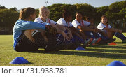 Купить «Female soccer team sitting on the ground while talking on soccer field. 4k», видеоролик № 31938781, снято 18 апреля 2019 г. (c) Wavebreak Media / Фотобанк Лори