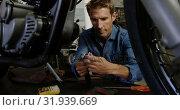 Купить «Male mechanic repairing motorbike in repair garage 4k», видеоролик № 31939669, снято 10 февраля 2019 г. (c) Wavebreak Media / Фотобанк Лори