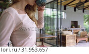 Купить «Woman drinking coffee and using mobile phone in kitchen at comfortable home 4k», видеоролик № 31953657, снято 12 марта 2019 г. (c) Wavebreak Media / Фотобанк Лори