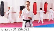 Купить «Preteen boy practicing karate movements with male trainer supervision», фото № 31956093, снято 3 июля 2020 г. (c) Яков Филимонов / Фотобанк Лори