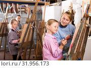 Купить «Female teacher helping girl during painting class», фото № 31956173, снято 21 августа 2019 г. (c) Яков Филимонов / Фотобанк Лори