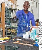 Купить «calm African American glazier choosing glass for cutting in workshop», фото № 31957605, снято 16 мая 2018 г. (c) Яков Филимонов / Фотобанк Лори