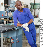 Купить «African American workman in blue overalls standing next to glass processing machine», фото № 31957609, снято 16 мая 2018 г. (c) Яков Филимонов / Фотобанк Лори