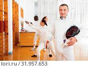 Купить «Active young male fencer in uniform standing with mask and foil at fencing room», фото № 31957653, снято 11 июля 2018 г. (c) Яков Филимонов / Фотобанк Лори
