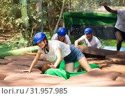 Купить «Team of friends overcomes an obstacle course in an amusement park», фото № 31957985, снято 25 августа 2019 г. (c) Яков Филимонов / Фотобанк Лори