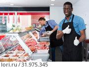 Купить «Happy African American seller of butcher store standing behind counter, giving thumbs up», фото № 31975345, снято 20 апреля 2018 г. (c) Яков Филимонов / Фотобанк Лори
