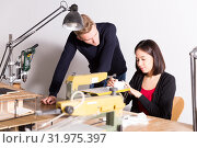 Купить «Teacher helping girl making architectural elements on scroll saw», фото № 31975397, снято 8 ноября 2018 г. (c) Яков Филимонов / Фотобанк Лори