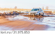 Купить «Russia, Samara, March 2019: A passenger car overcomes a muddy puddle in the spring thaw on a country road.», фото № 31975853, снято 30 марта 2019 г. (c) Акиньшин Владимир / Фотобанк Лори