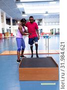 Купить «Female physiotherapist helping disabled man walk with prosthetic leg on ramp in sports center», фото № 31984621, снято 24 марта 2019 г. (c) Wavebreak Media / Фотобанк Лори