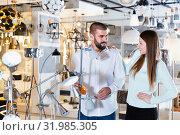 Купить «Smiling couple customers choosing floor lamp with a long standard in store», фото № 31985305, снято 29 января 2018 г. (c) Яков Филимонов / Фотобанк Лори
