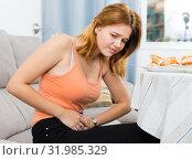 Female is overeating and she sitting unhappy. Стоковое фото, фотограф Яков Филимонов / Фотобанк Лори