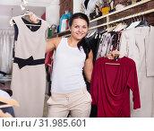 Купить «Young woman chousing dress at clothing store», фото № 31985601, снято 24 октября 2016 г. (c) Яков Филимонов / Фотобанк Лори