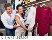 Купить «Family choosing dress and blouse at clothing shop», фото № 31985609, снято 24 октября 2016 г. (c) Яков Филимонов / Фотобанк Лори