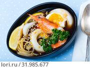 Купить «Image of spicy pan-Asian soup with squid, shrimp, egg noodles and sesame», фото № 31985677, снято 21 ноября 2019 г. (c) Яков Филимонов / Фотобанк Лори
