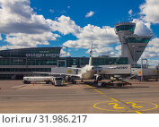 Helsinki Airport Finland 26.07.2019: Finnair airline technicians men load Luggage from container into the compartment in the tail of the aircraft. Two Airbus standing on the runway and waiting flight. Редакционное фото, фотограф Алексей Ширманов / Фотобанк Лори