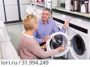 Купить «Smiling mature married couple are choosing washing machine», фото № 31994249, снято 10 июля 2020 г. (c) Яков Филимонов / Фотобанк Лори