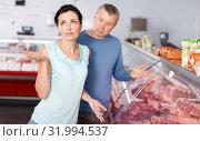 Купить «Sad adult couple customers choosing meat in shop», фото № 31994537, снято 22 июня 2018 г. (c) Яков Филимонов / Фотобанк Лори