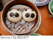 Купить «Round biscuits glazed like pandas in cookie box», фото № 32002817, снято 8 мая 2019 г. (c) Ekaterina Demidova / Фотобанк Лори