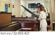 Купить «Portrait of pretty woman in music store», видеоролик № 32003421, снято 12 мая 2019 г. (c) Яков Филимонов / Фотобанк Лори