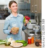 Купить «Smiling housewife cooking dinner in the kitchen at home», фото № 32009189, снято 21 ноября 2019 г. (c) Яков Филимонов / Фотобанк Лори