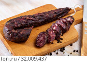 Купить «French tasty slicing dry-cured sausage with liver at wooden desk», фото № 32009437, снято 25 августа 2019 г. (c) Яков Филимонов / Фотобанк Лори