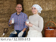 rural couple of farmers drinking milk in hayloft on farm. Стоковое фото, фотограф Татьяна Яцевич / Фотобанк Лори