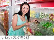 Купить «Happy girl in the store picks up candy in the bag», фото № 32010593, снято 25 апреля 2017 г. (c) Яков Филимонов / Фотобанк Лори