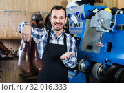 Купить «Male worker demonstrating repaired shoes in shoe», фото № 32016333, снято 2 февраля 2017 г. (c) Яков Филимонов / Фотобанк Лори