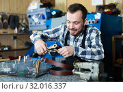 Купить «Smiling male worker shaping new hole in belt», фото № 32016337, снято 2 февраля 2017 г. (c) Яков Филимонов / Фотобанк Лори