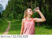 Female jogger quenches thirst. Стоковое фото, фотограф Евгений Харитонов / Фотобанк Лори