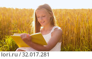 Купить «smiling young girl reading book on cereal field», видеоролик № 32017281, снято 4 августа 2019 г. (c) Syda Productions / Фотобанк Лори