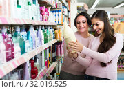 Купить «woman picking bottles with shampoo and conditioner from shelf in cosmetics store», фото № 32019525, снято 5 декабря 2019 г. (c) Яков Филимонов / Фотобанк Лори
