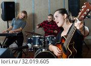 Купить «excited girl rock singer with guitar during rehearsal», фото № 32019605, снято 26 октября 2018 г. (c) Яков Филимонов / Фотобанк Лори