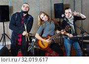 Купить «Three bandmates posing together with musical instruments in rehearsal room», фото № 32019617, снято 26 октября 2018 г. (c) Яков Филимонов / Фотобанк Лори