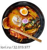 Купить «Traditional japanese noodle soup with shiitake mushroom, egg and greens served in ceramic bowl with wooden chopsticks», фото № 32019977, снято 22 января 2020 г. (c) Яков Филимонов / Фотобанк Лори