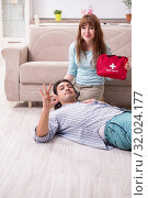 Купить «Young couple in first aid concept at home», фото № 32024177, снято 10 мая 2019 г. (c) Elnur / Фотобанк Лори