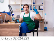 Купить «Young handsome contractor cleaning the office», фото № 32024229, снято 9 мая 2019 г. (c) Elnur / Фотобанк Лори