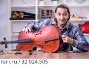 Купить «Young handsome repairman repairing cello», фото № 32024505, снято 4 апреля 2019 г. (c) Elnur / Фотобанк Лори