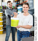 Купить «Young woman standing near man and holding bucket of paint in household store», фото № 32027037, снято 17 мая 2018 г. (c) Яков Филимонов / Фотобанк Лори