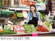 Купить «Woman seller displaying assortment», фото № 32027185, снято 18 марта 2017 г. (c) Яков Филимонов / Фотобанк Лори