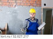 Купить «Male in the helmet ready is plastering the wall», фото № 32027217, снято 3 июня 2017 г. (c) Яков Филимонов / Фотобанк Лори