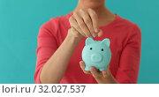 Positive female putting coin in piggybank, planning budget, financial savings. Стоковое видео, видеограф Ekaterina Demidova / Фотобанк Лори